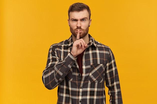 수염 난 잔인한 남자, 갈색 머리를 가진 불행한 남자. 체크 무늬 셔츠와 액세서리 착용. 침묵 기호를 표시하고 눈썹을 들어 올립니다. 노란색 벽 위에 절연