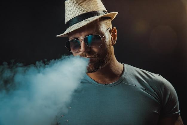 Бородатый брутальный мужчина в шляпе и солнечных очках курит парную сигарету вместо табака на черном