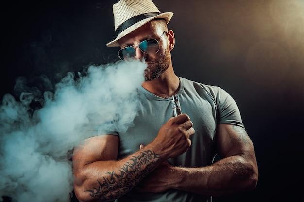 Бородатый брутальный мужчина в шляпе и солнечных очках курит парную сигарету вместо табачной студии, снятой на черном