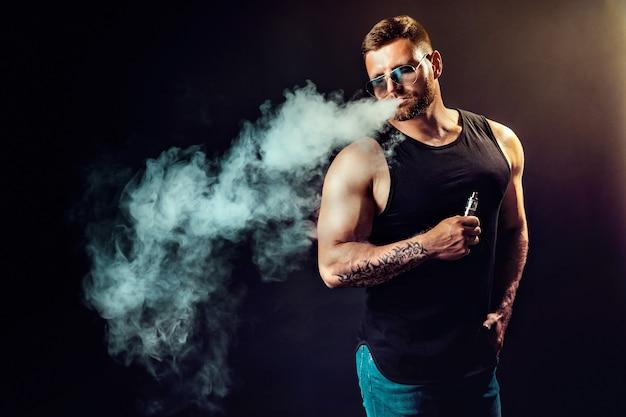 Бородатый брутальный мужчина в солнечных очках курит парную сигарету вместо табака на черном