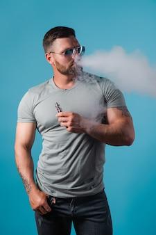 Бородатый брутальный мужчина в солнечных очках курит паровую сигарету вместо табака на синем