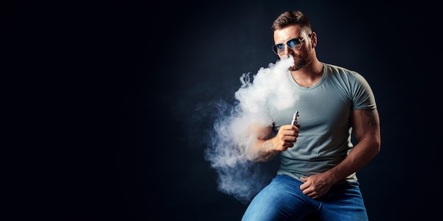 Бородатый брутальный мужчина в солнечных очках курит парную сигарету вместо табачной студии на черном