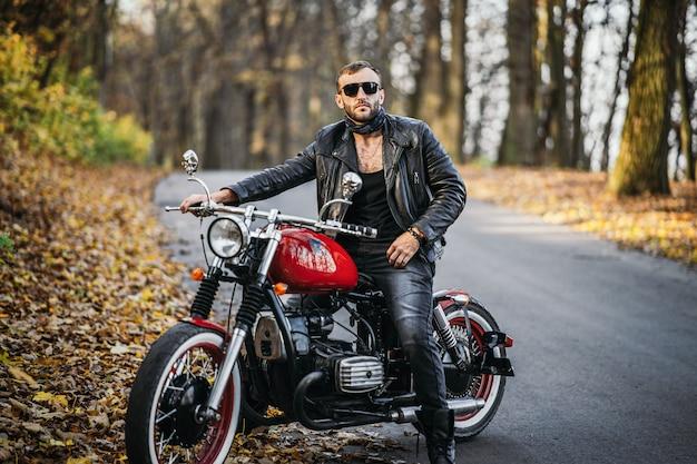 숲에서 도로에 오토바이에 앉아 선글라스와 가죽 재킷에 수염 난폭 한 남자