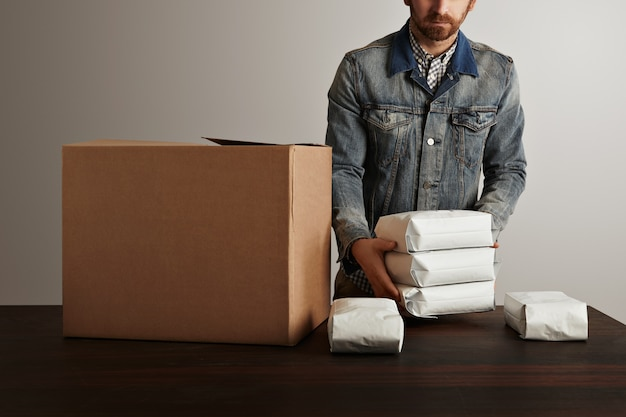 Bearded brutal man in jeans work jacket puts blank sealed hermetic packages inside big carton paper box on wooden table. special delivery
