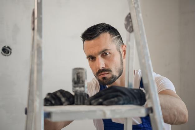 Бородатый строитель в униформе использует в работе электронную линейку