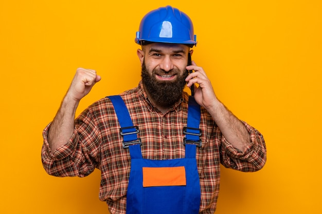 Uomo barbuto costruttore in uniforme da costruzione e casco di sicurezza felice ed eccitato pugno serrato sorridente mentre parla al telefono cellulare in piedi su sfondo arancione