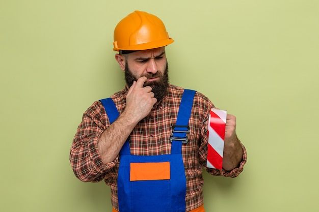 Bearded builder man in construction uniform and safety helmet holding adhesive tape looking at it intrigued standing over green background