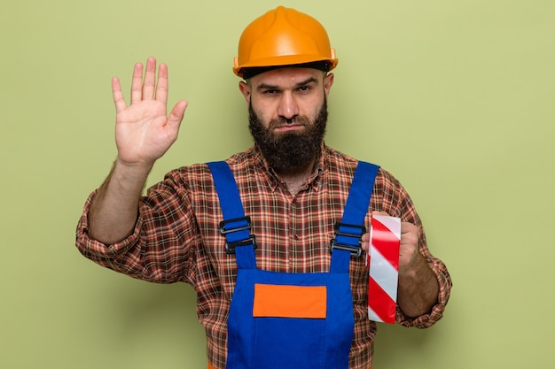 Bearded builder man in construction uniform and safety helmet holding adhesive tape looking with serious face making stop gesture with hand