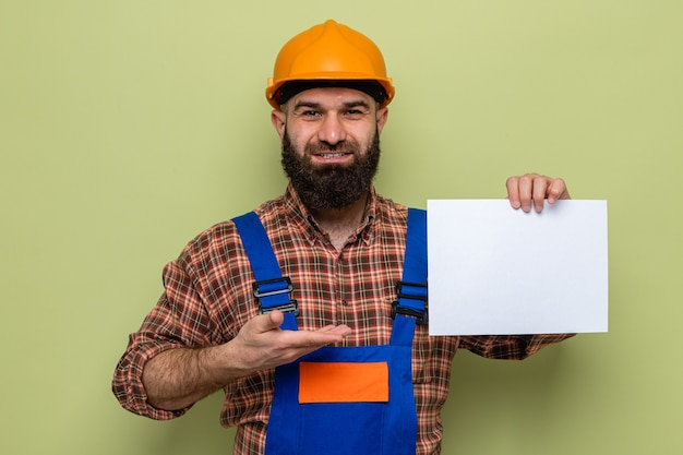 Bearded builder man in construction uniform and safety helmet holding blank page presenting with arm looking at camera smiling cheerfully standing over green background