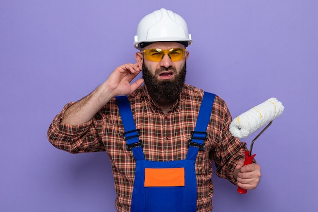 Bearded builder man in construction uniform and safety helmet holding paint roller looking at camera confused trying to hear holding hand near his ear standing over purple background