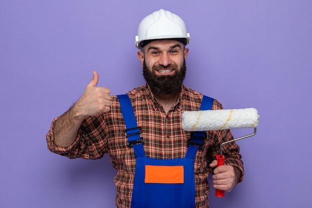 Uomo barbuto costruttore in uniforme da costruzione e casco di sicurezza che tiene il rullo di vernice guardando la telecamera sorridendo allegramente mostrando i pollici in su in piedi su sfondo viola