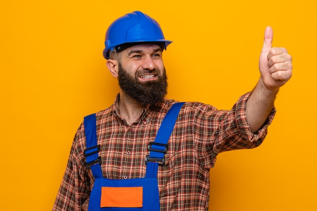 Bearded builder man in construction uniform and safety helmet looking aside smiling cheerfully happy and positive showing thumbs up