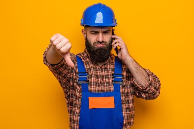 Uomo barbuto costruttore in uniforme da costruzione e casco di sicurezza che guarda l'obbiettivo dispiaciuto che mostra i pollici giù parlando al telefono cellulare in piedi su sfondo arancione