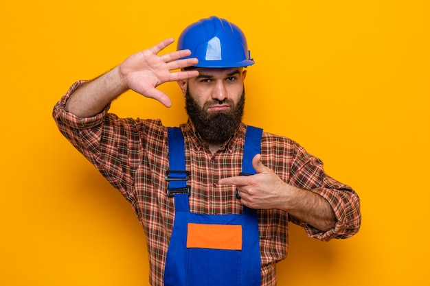 Bearded builder man in construction uniform and safety helmet looking at camera making frame with hands looking at camera through this frame standing over orange background