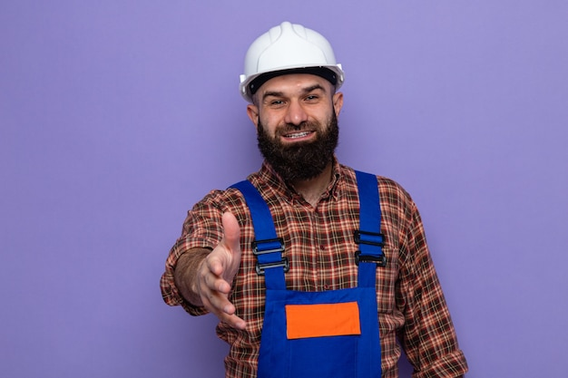 Bearded builder man in construction uniform and safety helmet looking at camera smiling cheerfully offering hand greeting gesture standing over purple background