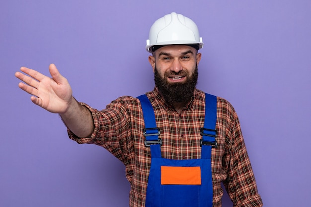 Bearded builder man in construction uniform and safety helmet looking at camera smiling cheerfully raising arm waving with hand standing over purple background