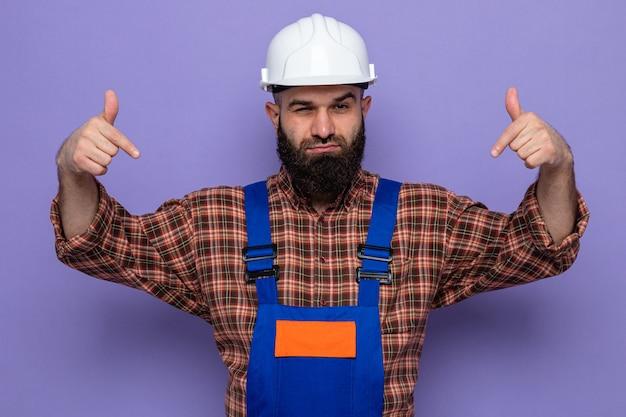 Uomo barbuto costruttore in uniforme da costruzione e casco di sicurezza che guarda la telecamera con espressione sicura che punta con l'indice verso il basso in piedi su sfondo viola
