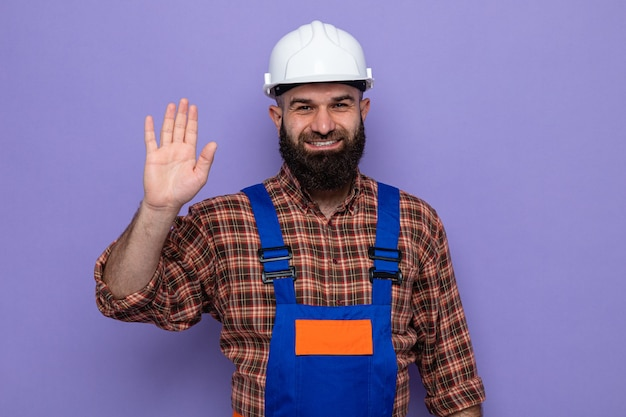 Uomo barbuto del costruttore in uniforme da costruzione e casco di sicurezza che sorride allegramente mostrando il quinto con il palmo