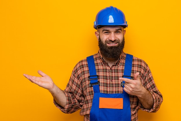 Uomo barbuto del costruttore in uniforme di costruzione e casco di sicurezza che sorride allegramente presentando qualcosa con il braccio della sua mano che indica con il dito indice al lato