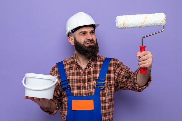 Uomo barbuto del costruttore in uniforme da costruzione e casco di sicurezza che sorride allegramente con un rullo di vernice