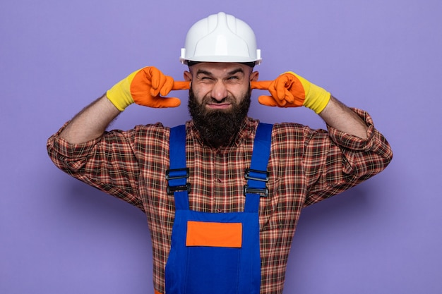 Bearded builder man in construction uniform and safety helmet wearing rubber gloves closing ears with fingers with annoyed expression standing over purple background