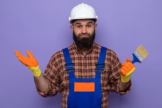 Uomo barbuto costruttore in uniforme da costruzione e casco di sicurezza che indossa guanti di gomma che tengono il pennello guardando la telecamera essendo confuso allargando le braccia ai lati in piedi su sfondo viola