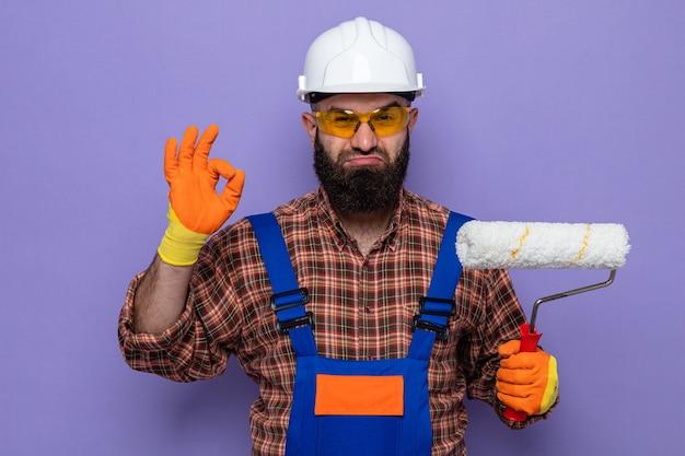 Uomo barbuto costruttore in uniforme da costruzione e casco di sicurezza che indossa guanti di gomma che tengono rullo di vernice guardando la telecamera felice e fiducioso che mostra segno ok in piedi su sfondo viola