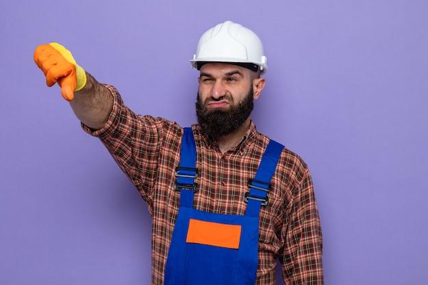 Uomo barbuto costruttore in uniforme da costruzione e casco di sicurezza che indossa guanti di gomma che guarda da parte essendo scontento mostrando i pollici verso il basso