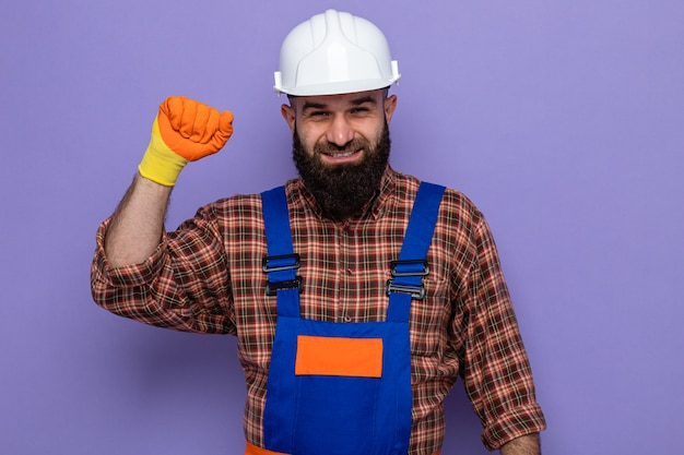 Uomo barbuto costruttore in uniforme da costruzione e casco di sicurezza che indossa guanti di gomma che guarda l'obbiettivo felice e fiducioso sorridente alzando il pugno come un vincitore in piedi su sfondo viola
