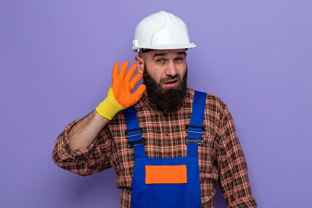 Uomo barbuto costruttore in uniforme da costruzione e casco di sicurezza che indossa guanti di gomma cercando incuriosito tenendo la mano sull'orecchio cercando di ascoltare i pettegolezzi in piedi su sfondo viola