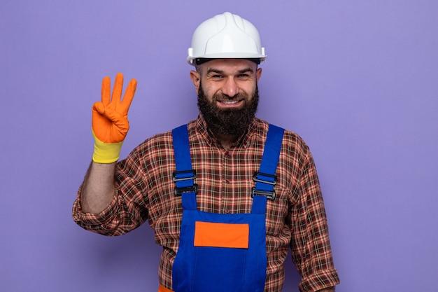 Uomo barbuto costruttore in uniforme da costruzione e casco di sicurezza che indossa guanti di gomma che sorride allegramente mostrando il numero tre con le dita