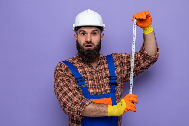 Uomo barbuto costruttore in uniforme da costruzione e casco di sicurezza che indossa guanti di gomma che sembra sorpreso a lavorare usando un metro