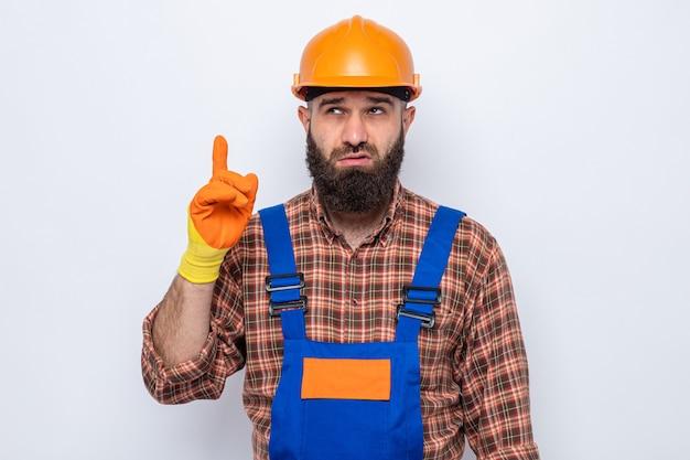 Uomo barbuto costruttore in uniforme da costruzione e casco di sicurezza che indossa guanti di gomma guardando in alto perplesso mostrando il dito indice in piedi su sfondo bianco