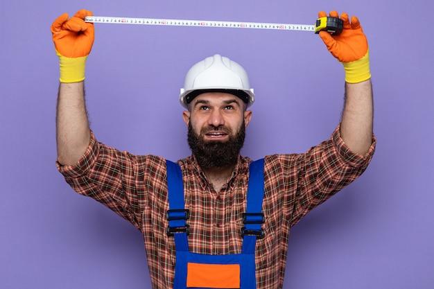 Uomo barbuto costruttore in uniforme da costruzione e casco di sicurezza che indossa guanti di gomma guardando in alto con espressione sicura di lavoro utilizzando nastro di misura in piedi su sfondo viola