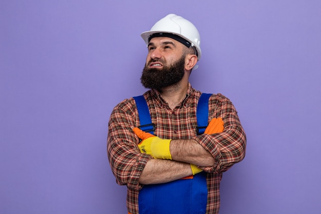 Uomo barbuto costruttore in uniforme da costruzione e casco di sicurezza che indossa guanti di gomma che osserva in su con il sorriso sul viso felice e fiducioso con le braccia incrociate sul petto in piedi su sfondo viola