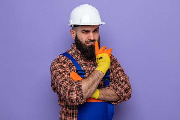 Bearded builder man in construction uniform and safety helmet wearing rubber gloves looking with serious face thinking