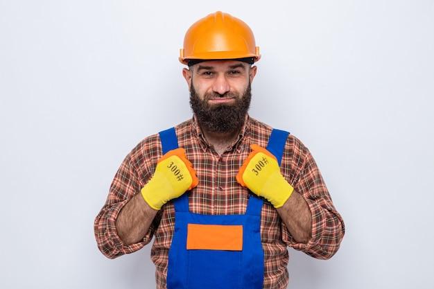 Uomo barbuto costruttore in uniforme da costruzione e casco di sicurezza che indossa guanti di gomma guardando con un sorriso sul viso felice