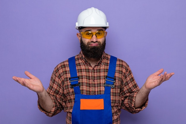 Bearded builder man in construction uniform and safety helmet wearing yellow safety glasses looking at camera confused spreading arms to the sides having no answer standing over purple background