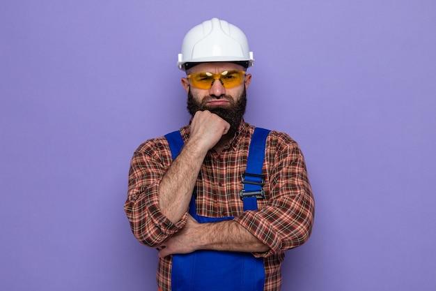 Uomo barbuto costruttore in uniforme da costruzione e casco di sicurezza che indossa occhiali di sicurezza gialli che guarda con la mano sul mento con la faccia arrabbiata