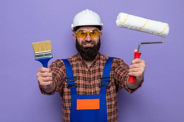 Uomo barbuto costruttore in uniforme da costruzione e casco di sicurezza in occhiali di sicurezza gialli che tengono rullo di vernice e pennello che guarda l'obbiettivo felice ed eccitato sorridente in piedi su sfondo viola