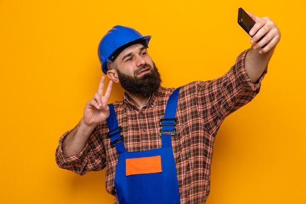 건설 유니폼을 입은 수염 난 건축업자와 안전 헬멧을 쓴 스마트폰을 사용하여 셀카를 하고 주황색 배경 위에 서 있는 v-sign을 즐겁게 보여주며 웃고 있습니다.
