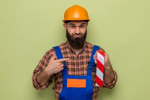 緑の背景の上に立っている顔に懐疑的な笑顔で人差し指で指している粘着テープを保持している建設制服と安全ヘルメットのひげを生やしたビルダーの男