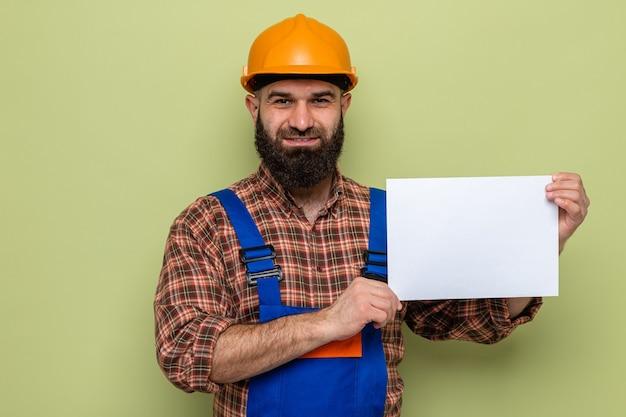 쾌활하고 행복하고 긍정적인 미소를 보이는 빈 페이지를 들고 건설 유니폼과 안전 헬멧에 수염된 빌더 남자