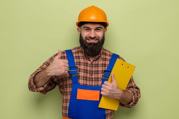 Бородатый мужчина-строитель в строительной форме и защитном шлеме с буфером обмена, глядя в камеру, весело улыбаясь, показывая большие пальцы руки вверх, стоя на зеленом фоне