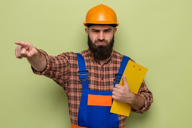Бородатый строитель в строительной форме и защитном шлеме с буфером обмена смотрит в камеру с хмурым лицом, указывая указательным пальцем на что-то стоящее на зеленом фоне