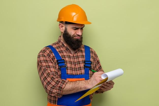 건설 유니폼을 입은 수염난 빌더 남자와 녹색 배경 위에 자신감을 보이는 메모를 만드는 빈 페이지가 있는 클립보드를 들고 있는 안전 헬멧