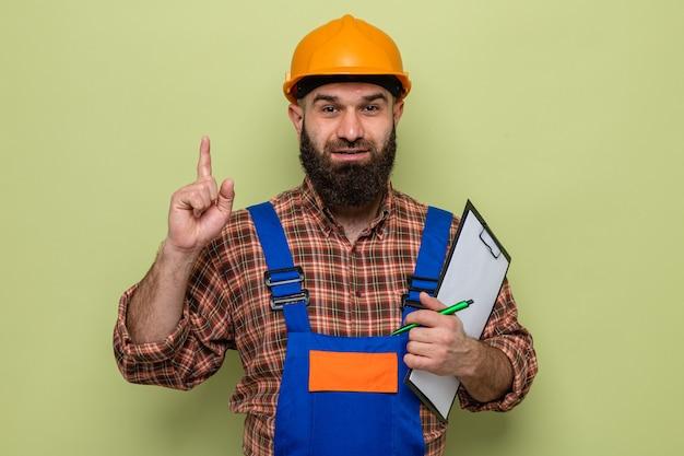 Бородатый мужчина-строитель в строительной форме и защитном шлеме держит буфер обмена с ручкой, глядя, показывая указательный палец, уверенно улыбаясь