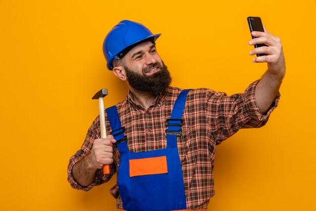 オレンジ色の背景の上に元気に立って笑顔のスマートフォンを使用してselfieを行う建設制服と安全ヘルメット保持ハンマーでひげを生やしたビルダー男