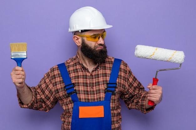 건설 유니폼을 입은 수염 난 건축업자, 페인트 롤러와 브러시를 들고 있는 안전 헬멧은 보라색 배경 위에 서서 선택을 하려고 하는 혼란스러워 보입니다.