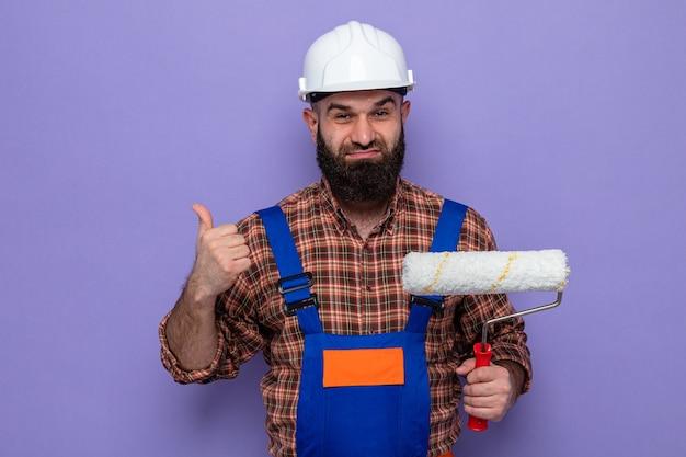 Бородатый мужчина-строитель в строительной форме и защитном шлеме, держащий валик с краской, выглядит уверенно улыбаясь и показывает палец вверх